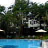 El área de la piscina del hotel Jacaranda con su jardín y las mesas del restaurante y cafetería forman un espacio delicioso