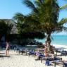 Imagen de la playa con marea alta. Al fondo se puede ver el restaurante a la carta.